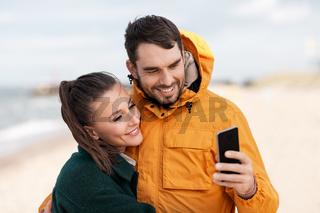 couple with smartphone on autumn beach