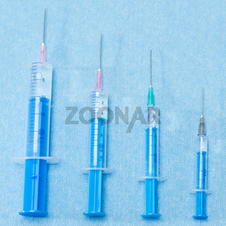 Hypodermic needles injections on blue medical cloth