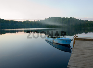 boat reflecting in calm waters of forest lake