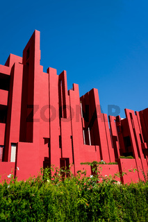 Geometric architecture of the postmodern apartment building 'La Muralla Roja', the red wall, by architect Ricardo Bofill in Calpe, Spain