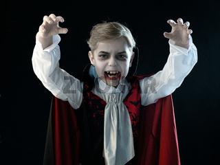 Boy in Halloween vampire makeup costume