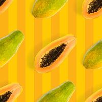 Fresh ripe papaya seamless pattern on orange background. Tropical abstract background. Top view.