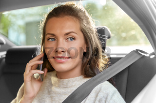 happy smiling woman in car calling on smartphone