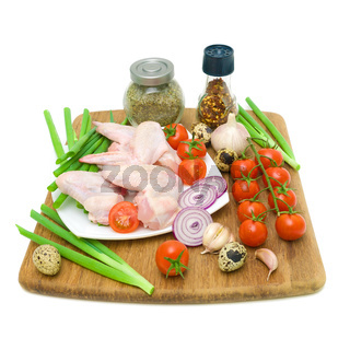 vegetables, quail eggs and raw chicken wings on a white background