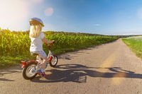 Young blond girl on her little bicycle on a road in rural landscape on a sunny day in spring
