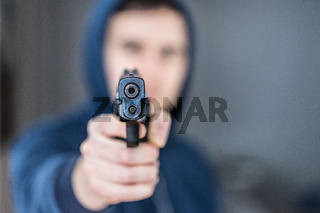 Crime or robbery concept: Man with black gun is aiming with his weapon