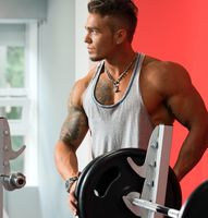 Handsome bodybuilder posing in gym with barbell