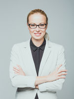 Business woman standing with arms crossed against gray background.