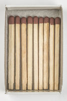Overhead close-up of 9 brown-tipped regular household safety matches in open matchbox