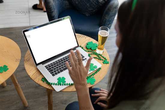 Caucasian woman holding beer on st patrick's day laptop video call with copy space on screen