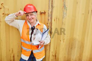 Stolze Frau mit rotem Schutzhelm und Klemmbrett