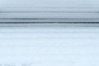 A snow covered bench with a black line