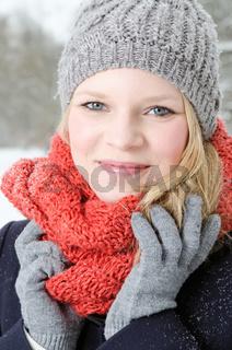 junge blonde Frau mit Mütze und Schal Winterwald Portrait