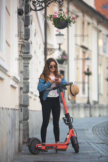 Electro-mobility. Traveler unlocking an e-scooter using an app on her smartphone. Traveler exploring old town on environmentally friendly electric scooter