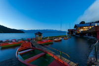 Rental row boats on pier at mountain lake Walchensee in Bavaria, Germany at dawn in early morning with boat house