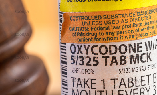Oxycodone opioid tablets with judge gavel for court decision about liability