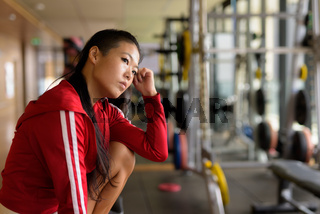 Serious Asian rebel woman thinking and sitting at gym