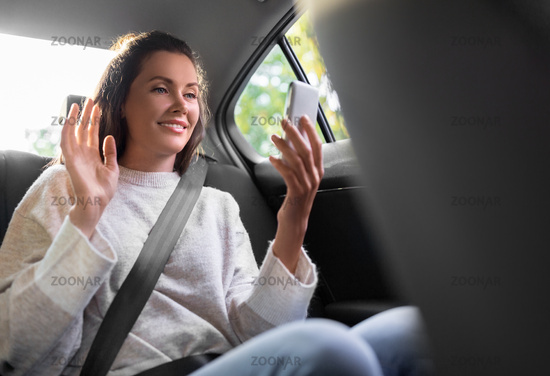 woman in taxi car having video call on smartphone