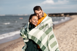 happy couple in warm blanket on autumn beach