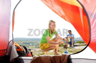 Camping young couple outside tent cook meal
