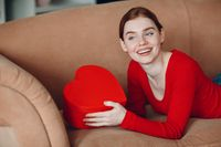 Beautifil young woman with red hair lying in her sofa in living room and holding the gift box in the shape of heart and smile. Valentines Day or Birthday