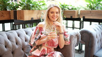 Woman drinking fresh beverage on sofa