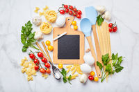Pasta cooking background with chalkboard, tomatoes, herbs, mushrooms, eggs, top view. Italian cuisine concept