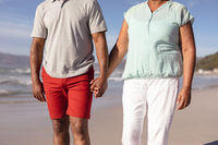 Mid section of african american couple holding hands standing on the beach