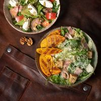 Salmon salads with mozzarella cheese and grilled slices of fruits stands on a table covered with a leather rag. Restaurant concept. Square cropped image. KETO diet concept. Whole30 concept