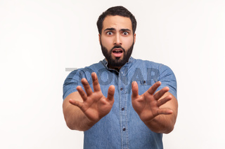 Emotional young bearded man on gray background.