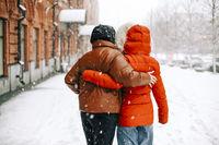Unrecognizable female friends walking on street in winter