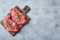 Two Fresh Raw meat Prime Black Angus Beef Steaks, Rib Eye, Denver, on wooden cutting board.