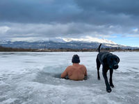 hardy man in ice water with snow with black dog