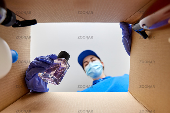 woman in mask packing parcel box with cosmetics