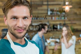 Portrait of smiling waiter and customers in background