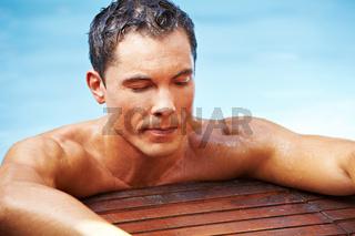Mann entspannt im Pool