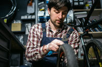 Technical expertise taking care bicycle shop. Handsome young mechanic fixing cycle wheel in workshop. Handsome repairman in workwear serving mountain bicycle. Male engineer adjusting velocipede