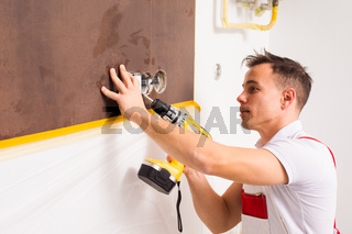 The electrician with a drill fastens the socket