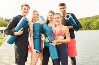 Sportliche Teenager mit Yogamatten am Seeufer