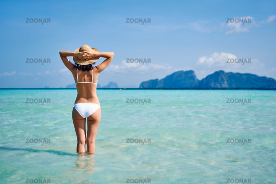 Rear view of a beautiful young woman enjoyi warm tropical ocean water with copy space.