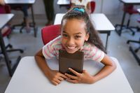 African american girl smiling while holding digital tablet sitting on her desk in class at school