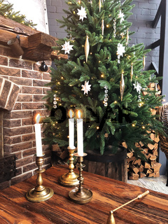 Burning candles in vintage metal candlesticks on wooden table near decorated for christmas tree