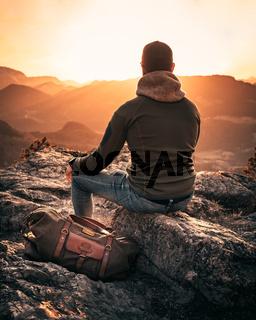 man with travel bag on mountain top enjoying sunset