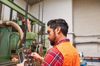 Arbeiter am Bedienfeld der Koordinatenbohrmaschine