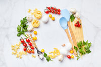 Food background with place for text, with different kinds of pasta, tomatoes, herbs, mushrooms, eggs, seasonings scattered on light marble background, top view.