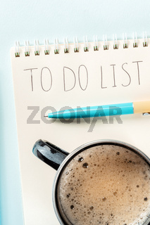 To do list. A paper notebook with a blue pen and with coffee, shot from the top
