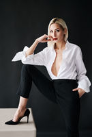Sexy blonde woman with red lips wearing white shirt and black classic pants posing on black studio background.