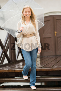 Woman stepping down the stairs with umbrella