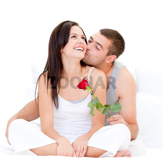 Pretty couple kissing each other against a white background