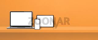 Laptop, mobile phone and digital tablet pc on orange wall shelf. Banner background